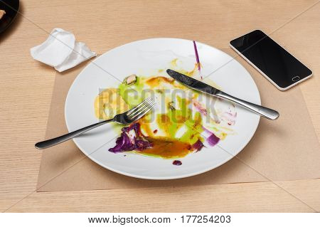 empty dish after food and smartphone on the wooden table, top view