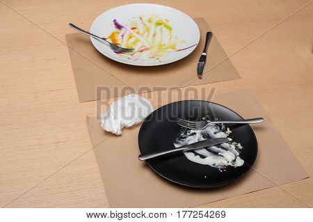 two white and black empty dishs after food on the wooden table, top view