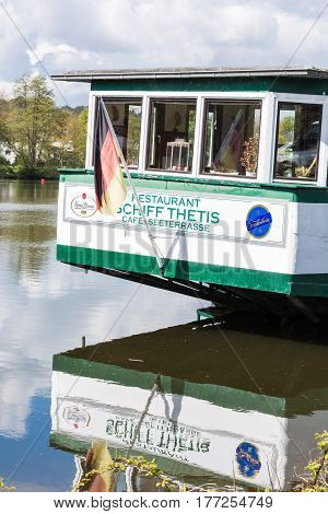 ESSEN KETTWIG NRW GERMANY - APRIL 28 2016: Back view of the cafe and restaurant ship Tetris in the city of Essen district of Kettwig am Stausee. Directly in front of the dam anchored the Thetis since the 1950s.