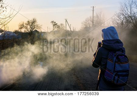 Village in smoke. Photographer takes picture of smoky road in evening sun. Rural landscape in spring