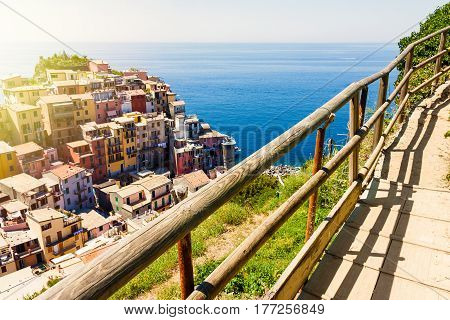 Manarola town view in Cinque Terre Italy with mountain trekking trail in foreground