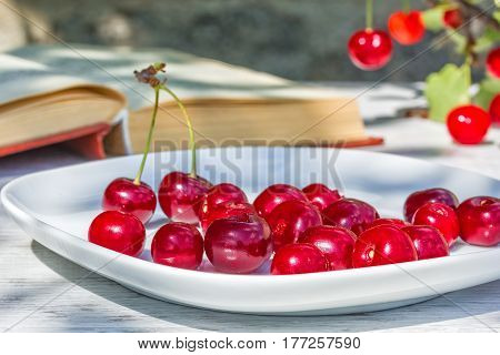 Red ripe cherries on a white plate and a book on a wooden table in the garden on a sunny summer day close-up. Focus on the foreground the background is blurred
