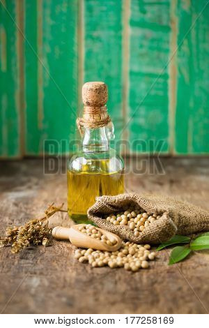 Soy bean and soy oil on wooden table. Selective focus.