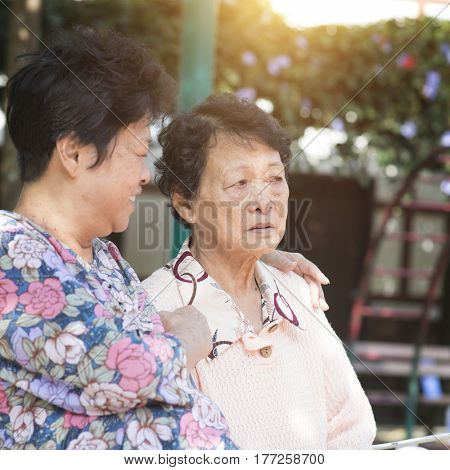 Candid shot of Asian senior adult women chatting at outdoor park in the morning.