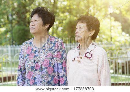 Candid shot of Asian elderly women walking at outdoor garden park in the morning.