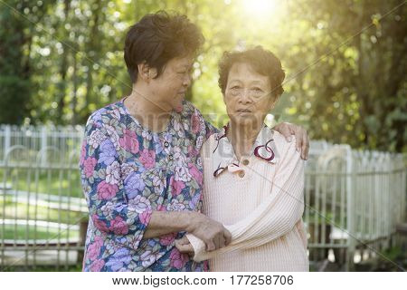 Candid shot of Asian elderly women holding hands at outdoor park in the morning.