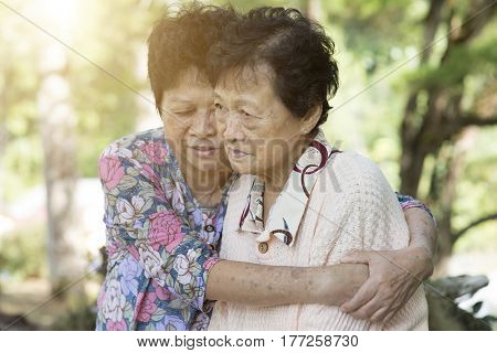 Candid shot of Asian elderly woman consoling her friend at outdoor park in the morning.