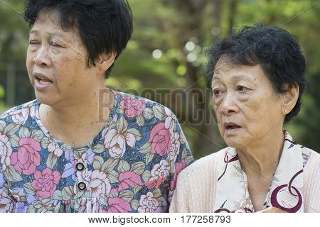Candid shot of Asian elderly women chatting at outdoor park in the morning.