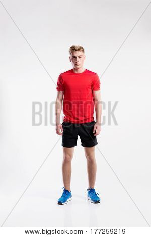 Handsome hipster fitness man in red t-shirt and black shorts. Studio shot on gray background.