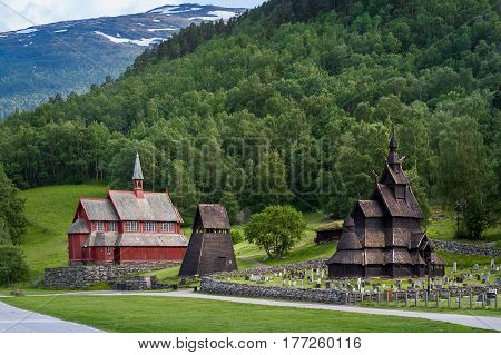 Old wooden Borgund Stave Church, bell tower and new church building historical complex view. Borgund, Norway.