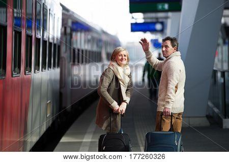 Beautiful senior couple on trainstation pulling a trolley luggage, waving.