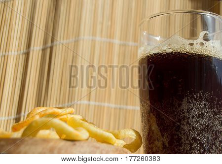 Plate of chips, a glass of dark beer with foam, bubbles on wooden background.