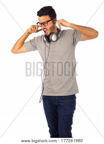 Young man facing loud sounds isolated on white