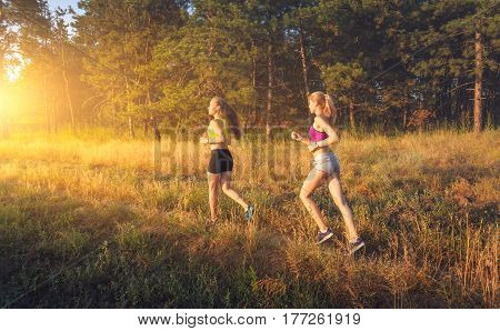 Young sporty girls running on a field near the trees at sunset in summer. Athlete running on the off road in the evening. Active woman. Sport and healthy lifestyle. Jogging fitness. Women runners