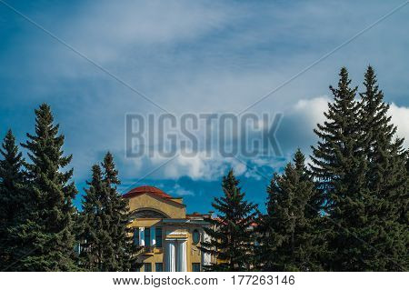 Scenic sunny sky with brights clouds with eastern pines and antic building in Saint  Petersburg botanical garden