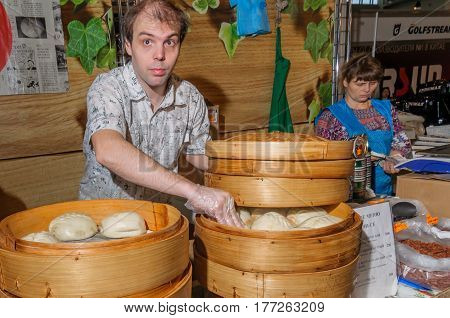 Moscow, Russia - February 25, 2017: Cook prepares national Korean fast food pyan-se in a traditional bamboo steamer