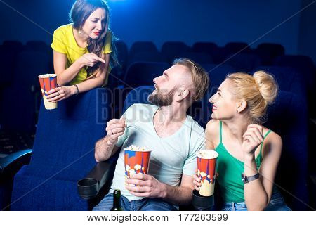 Woman swearing on the couple talking loudly on the front seats in the cinema