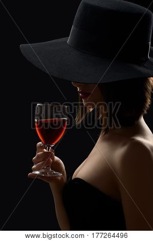 Wine lover. Vertical portrait of a classy woman in a black dress and a hat having a glass of red wine mystery mysterious shadow anonymous hidden hiding face elegance grace sexy hot seduction concept