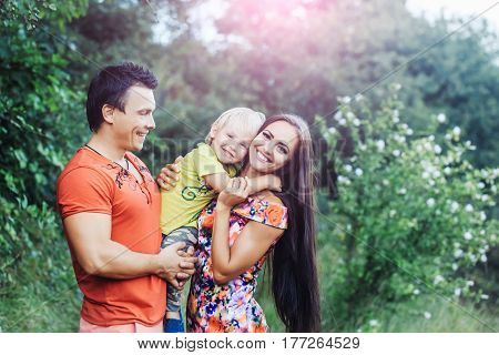 Happy smiling family of cute baby boy little child in mother and father hands in green park on sunny summer day outdoors on natural background