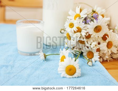 Simply stylish wooden kitchen with bottle of milk and glass on table, summer flowers camomile, healthy foog moring concept noone close up