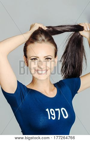 Pretty girl or beautiful woman with happy smiling face and long brunette hair ponytail in stylish blue tshirt with 1970 number numeral print design posing on grey background