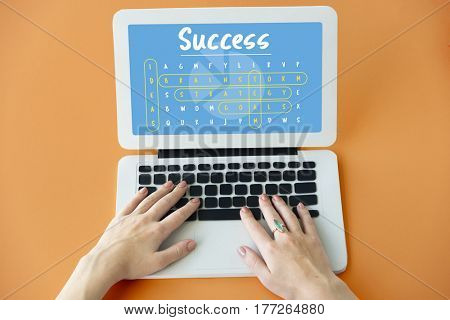 Hands using laptop with success and wordsearch