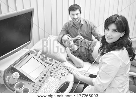 Black and white shot of a gynecologist and her pregnant patient with husband smiling to the camera during ultrasonic scanning fetal life checkup at the hospital professionalism lifestyle pregnancy.
