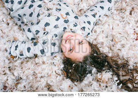 Cute happy little girl in pajama lying on floor covered with down or fluff and feather natural soft fluffy plume on textured background
