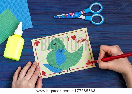 Making a greeting card for Mother's Day. Children's art project. DIY concept. Step-by-step photo instruction. Step 8. Completion of design card. Inscription: I love mom
