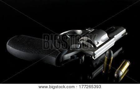 Revolver on a dark reflective background with ammunition at the side