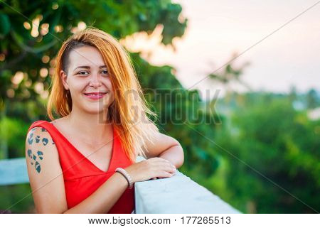 A lady in red smiles at the verandah of a summer restaurant. Beautiful happy girl with shaved temples in a red dress and with red lipstick.