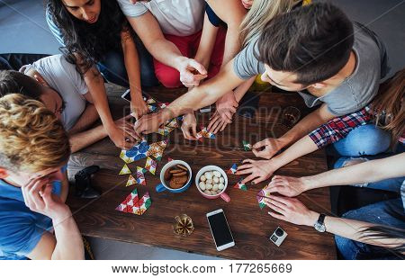 Top View Creative Photo Of Friends Sitting At Wooden Table.  Having Fun While Playing Board Game
