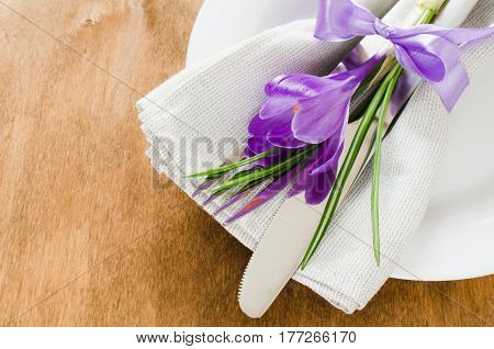 Spring Festive Table Setting With Fresh Flower. Napkin plate and cutlery on wooden table. Holidays background. Selective Focus.