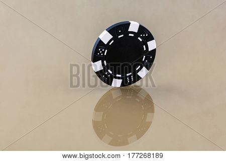 On the reflecting surface is a black casino chip