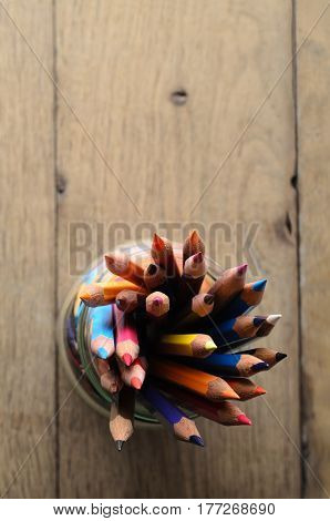 Overhead shot of art pencils in many colours grouped in a glass jar on wooden planked table with copy space above.