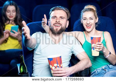 Dissatisfied couple watching film sitting in the cinema