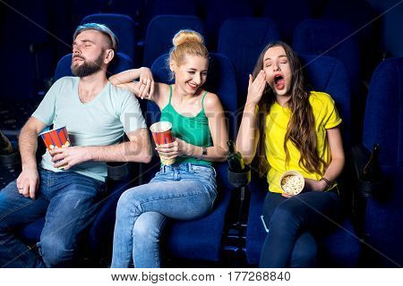 Friends sleeping during boring film in the cinema