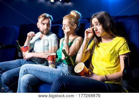 Friends crying watching sad film in the cinema