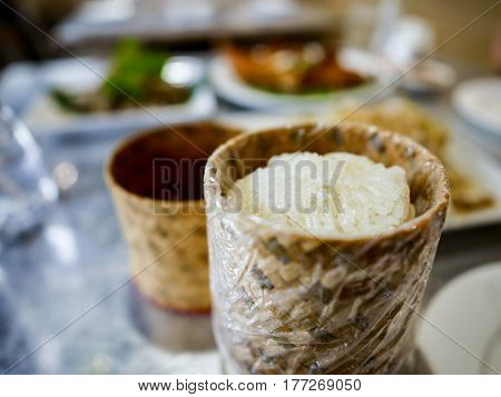 Sticky rice in the traditional crafted container with Som Tum