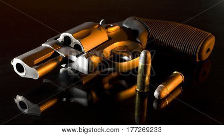 Revolver with cartridges on a dark background with orange side lighting