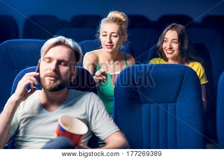 Rude man talking with phone disturbing women on the back seats in the cinema