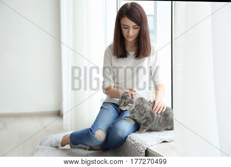 Beautiful young woman with cute cat sitting on window sill at home