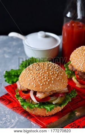 Homemade hamburger with beef tomatoes and lettuce on a concrete background. Fast food.