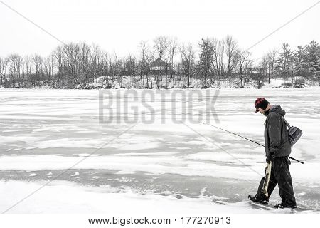 Outdoor fisherman walking across a frozen lake in winter carrying his gear and a log