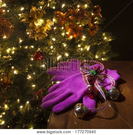 Pink Christmas gloves with bells on a table next to a decorated tree