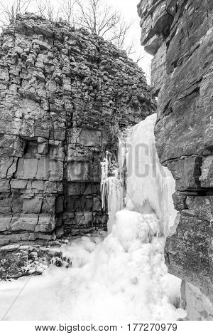 Frozen waterfall spilling out between two high natural layered rock walls black and white winter scene