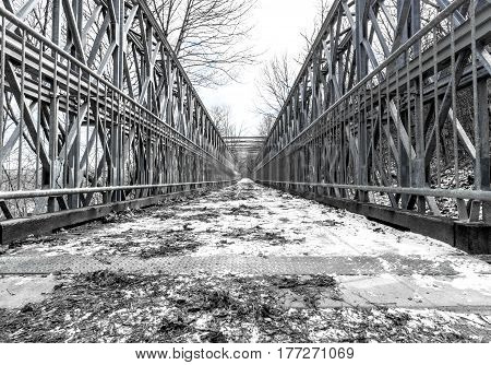 Snow covered symmetrical metal foot bridge in winter balanced composition in greyscale and blue