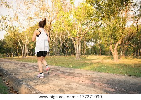 Young woman running in wood training and exercising for trail run marathon endurance in morning sunrise. Fitness healthy lifestyle concept. Vintage effect style pictures.