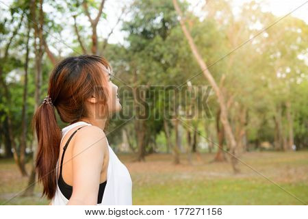 Portrait of beautiful smiling young woman enjoying yoga relaxing feeling alive breathing fresh air got freedom from work or relations calm and dreaming with closed eyes in green park copy space