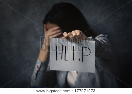 Woman holding sheet of paper with word HELP on grey wall background